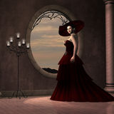 Lady in Red Dress. A beautiful woman in a red gown poses near a window of a pink marble room Stock Photos