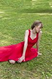 Lady in red dress. Beautiful lady in red are sittiing on green grass Royalty Free Stock Image