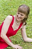 Lady in red dress. Beautiful lady in red are sittiing on green grass Royalty Free Stock Photos