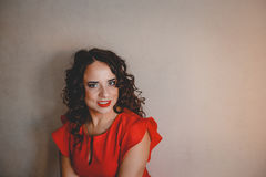 Lady in a red dress. Clouseup, curly and dark hair Royalty Free Stock Photos