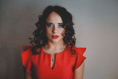 Lady in a red dress. Clouseup, curly and dark hair Stock Images