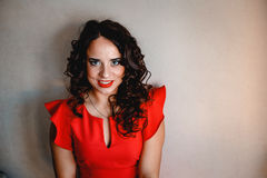 Lady in a red dress. Clouseup, curly and dark hair Royalty Free Stock Image