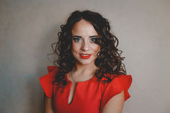 Lady in a red dress. Clouseup, curly and dark hair Royalty Free Stock Photography