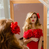 Lady in red dress with flower barrette looking in Stock Photos