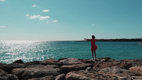 Lady in red dress with hands apart standing on rocky cliffs pier looking at blue sea on sunny day. Red dress flapping on wind and. Sun reflecting on water stock footage