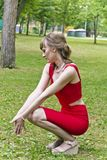 Lady in red dress. Lady in red are sitting on squat Royalty Free Stock Photo