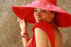 The lady in red with fantastic hat. Portrait of beautiful women with stunning glowing  eyes and big red hat under the sunlight Royalty Free Stock Image