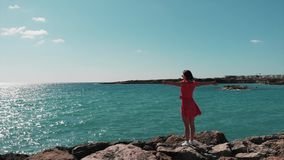 Lady in red flapping on wind dress standing on rocky beach cliff pier with hands apart on sunny summer day at cyprus coral bay. Ae stock footage