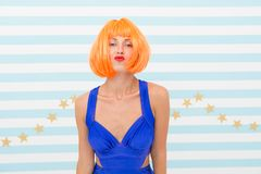 Lady red or ginger wig posing in blue dress. Actress skills concept. Woman kiss face expression. Lady actress practicing. Performance. Girl posing striped stock photo