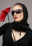 Lady in red gloves with crop. Portrait of lady in black headscarf and red gloves with crop stock photo