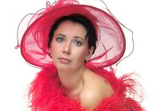 Lady in red hat. Portrait of a beautiful young woman wearing a red hat and feathered red boa over naked shoulders Royalty Free Stock Photo