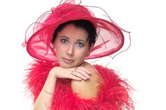 Lady in red hat. Portrait of a beautiful young woman wearing a red hat and feathered red boa over naked shoulders with copyspace Royalty Free Stock Image