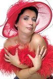 Lady in red hat embrassing herself. Portrait of a beautiful young woman wearing a red hat and feathered red boa over naked shoulders Royalty Free Stock Images
