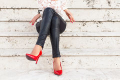 Lady with red high heel shoes sitting on stairs Stock Photography