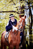 Lady on a red horse. Lady on a horse. The lady on riding walk. The woman astride a horse. The aristocrat on riding walk royalty free stock image
