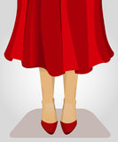 Lady in red. Legs of a woman clothed in red skirt and res shoes Stock Photo