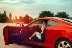 Lady with red lips sits in red sport car Stock Images