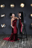 Lady in red and magic mirror Royalty Free Stock Images