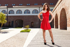 Lady in red outdoor. Handsome girl dressed in red short skirt standing outside in urban landscape in a sunny day Stock Photos