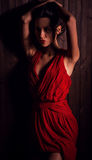 Lady in red pose on wooden background. Royalty Free Stock Photos
