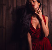 Lady in red pose on wooden background. Royalty Free Stock Photography