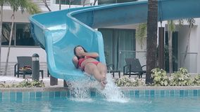 Lady in red swimsuit slides down blue plastic water slide stock footage