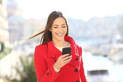 Lady in red uses a smart phone in winter in the street. Lady in red uses a smart phone in winter walking in the street of a coast town stock photos
