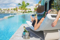 Lady relaxing in deck chair by the pool and drinking champagne Stock Images