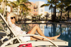 Lady relaxing in deck chair by the swimming pool Royalty Free Stock Photography