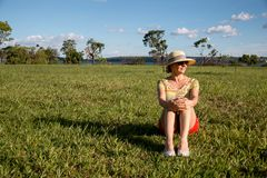 Lady Relaxing on the Grass. Wearing a Hat and Shorts Enjoying the Great Outdoors Royalty Free Stock Images