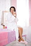 Lady relaxing after massage sitting on couch in nice salon. Young woman in white bathrobe and pink slippers having hot drink after massage. Body care stock photography