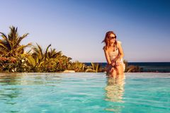 Lady relaxing at swimming pool Stock Photos