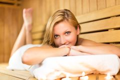 Lady relaxing in traditional wooden sauna. royalty free stock photo