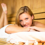 Lady relaxing in traditional wooden sauna. Royalty Free Stock Image