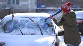 Lady removing snow from windshield with snow brush stock video footage