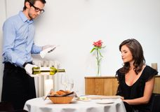 Lady in restaurant. Waiter offering wine to lady in restaurant royalty free stock photos