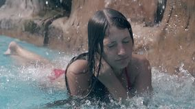 Lady rests under artificial waterfall and straightens hair. Tanned lady in red swimsuit rests under artificial waterfall and straightens long dark wet hair close stock video