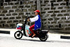 A lady rides her e-bike or electronic bike on an uphill road in Antipolo City. Royalty Free Stock Images