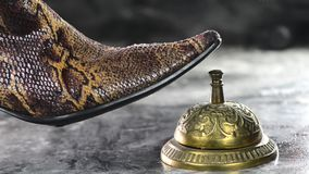 Lady ringing service bell. Lady in snake skin boots ringing brass service service bell stock footage