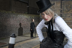Lady Ripper in London street. Street Fashion shot of woman in late victorian clothes with man in the background Stock Image