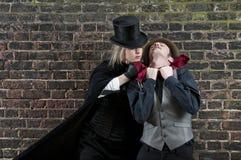 Lady ripper strangling man. Fashion shot of woman  dressed as Jack the Ripper strangling man Stock Image