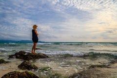 Lady on rocks on the coast, Boracay Island, Philippines Royalty Free Stock Photo