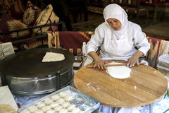 A lady rolls Turkish flat bread before placing it onto a hot plate cooker. Royalty Free Stock Photo