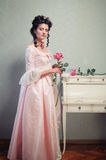 Lady with a Rose. A young brunette lady in a pink ancient dress holding a rose Royalty Free Stock Photography