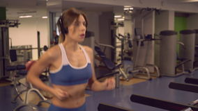 Lady run on training machine in sport club. Happy woman running listening music in gum. Young girl training on a treadmill using headphones. Caucasian athlete stock video