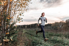 Lady running in autumn forest Stock Images