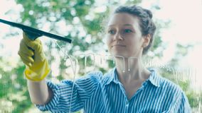 Lady runs black squeegee on wet window and shows thumb-up stock footage