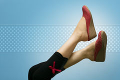 Lady's attractive feet with polka dotted shoes. Attractive feet high up, showing red polka dotted shoes, against a vignette blue background with polka dots Royalty Free Stock Images