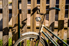 Lady's bicycle. Closeup of lady's vintage bicycle propped up against a slatted wooden fence showing dynamo, bell, light and pump Royalty Free Stock Image