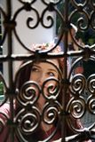 Lady through ornate window bars stock photo